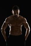 Mycket muskulös man som poserar med den nakna torson i studio Arkivfoton