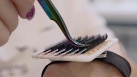 Mycket närbild av härliga apparater och delar i skönhetsalongen Stylisten visar en uppsättning av falska ögonfrans stock video
