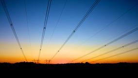 Mycket nätta powerlines på solnedgången Arkivbild