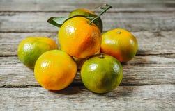 Mycket ny mandarin eller mandarine med gröna blad på trägolv Arkivbild