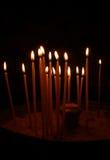 Mycket oflighted stearinljus i mörkret Arkivfoto