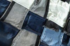 Mycket olika modeller av jeans som lägger på golvet Flätat samman med de royaltyfria bilder
