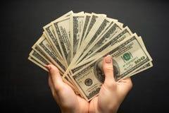 mycket pengar i händerna, oss dollar, på en svart bakgrund arkivfoto