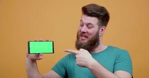 Mycket positiv attraktiv punkt för ung man på hans gröna skärm för telefoner arkivfilmer