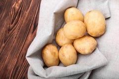 Mycket rå och unga potatisar på ett ljus - grå färger plundrar och på en träbakgrund för mörk brunt Rå, rena nya nya potatisar Arkivfoto