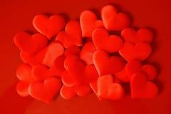 Mycket röda hjärtor för satäng på en röd yttersida St Valentindag Lyckönskan på valentindag royaltyfri foto