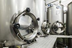 Mycket rostfritt stålbehållare med stora runda luckor, modern dryckproduktion Royaltyfri Fotografi