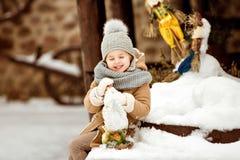 Mycket sött och roligt flickabarn i ett beige lagsammanträde på set Arkivfoton