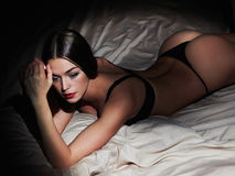 Mycket sexig brunettkvinna som poserar i svart damunderkläder i säng Den varma kvinnan med perfekt bantar kroppen Arkivfoton