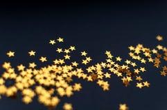 Mycket små guld- stjärnor på en svart bakgrund, en bästa sikt, en karneval, en nattpartiinbjudan eller festlig bakgrund, himmel f fotografering för bildbyråer