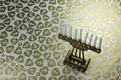 Mycket små mässingsChanukkahmenoror med vitstearinljus på en bakgrund av metalliska bladguld Arkivbild