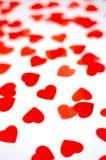 Mycket små röda hjärtor på en isolerad bakgrund arkivfoto