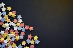 Mycket socker färgade stjärnor på hörn av den svarta bakgrundsmakroen, bakgrund för konditor med copyspace royaltyfri bild