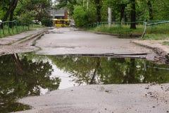 Mycket stor djup grop med vatten för den hela bredden av vägen efter avkloppreparationen royaltyfri fotografi