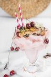 Mycket stor galen milkshake med körsbärsröda bär med ett stycke av c Royaltyfri Bild