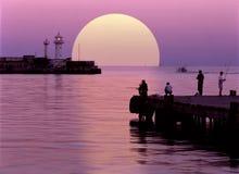 Mycket stor sol dubbel exponering Fiskare på en bakgrund av inställningssolen royaltyfri bild