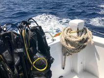 Mycket svart dykningdräkt med slangar och dykningomslag hänger på ställningen, och ett tungt rep på ettflyttning fartyg, sänder,  arkivfoto