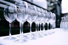Mycket tomma vinexponeringsglas på tabellen Royaltyfri Foto