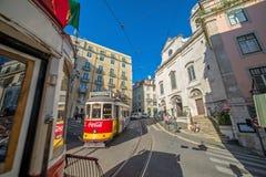 Mycket touristic ställe i den gamla delen av Lissabon, med en traditionell spårvagn som förbigår i staden av Lissabon, Portugal Arkivbild