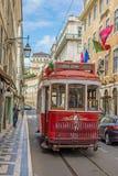 Mycket touristic ställe i den gamla delen av Lissabon, med en traditionell spårvagn som förbigår i staden av Lissabon, Portugal Arkivfoton