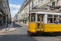 Mycket touristic ställe i den gamla delen av Lissabon, med en traditionell spårvagn som förbigår i staden av Lissabon, Portugal Arkivfoto