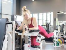 Mycket trött kvinnlig i activewearen som sitter på bänk royaltyfri foto