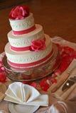 Mycket trevlig bröllopstårta med rosa isläggning Arkivfoton