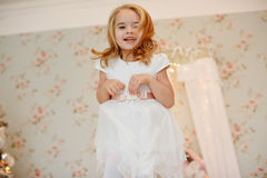 Mycket trevlig charmig liten flickablondin i den vita klänningen som hoppar upp arkivfoton