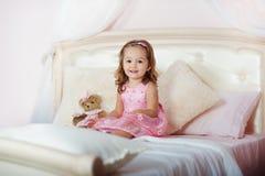 Mycket trevlig charmig liten flickablondin i rosa färgklänning med nallebjörnen som högt sitter på en säng och skratt för barn` s Fotografering för Bildbyråer