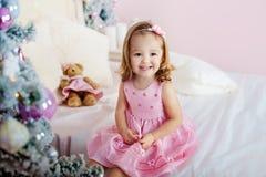 Mycket trevlig charmig liten flickablondin i rosa färgklänningsammanträde på en säng och skratt för barn` s högt bakgrunden av Arkivbilder