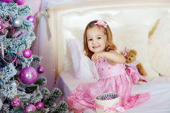 Mycket trevlig charmig liten flickablondin i rosa färgklänningsammanträde på en säng och skratt för barn` s högt bakgrunden av Arkivfoton