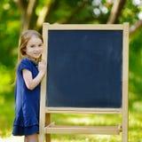 Mycket upphetsad liten skolflicka vid en svart tavla Royaltyfri Bild