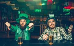 Mycket upprivna ypungmän visar stora tummar ner och ser upp De sitter på stångräknaren i bar Grabb på vänstra kläder St Patrick royaltyfria bilder