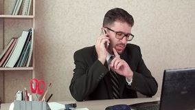 Mycket upptagen kontorschef, svar två telefoner på en gång arkivfilmer