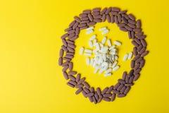 Mycket violet, ovala minnestavlor, spridda preventivpillerar, spridde på en gul bakgrund i form av en cirkel, i mitt av ciren Arkivbilder