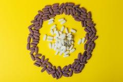 Mycket violet, ovala minnestavlor, spridda preventivpillerar, spridde på en gul bakgrund i form av en cirkel, i mitt av ciren Arkivfoto