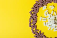 Mycket violet, ovala minnestavlor, spridda preventivpillerar, spridde på en gul bakgrund i form av en cirkel, i mitt av ciren Royaltyfri Fotografi