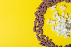Mycket violet, ovala minnestavlor, spridda preventivpillerar, spridde på en gul bakgrund i form av en cirkel, i mitt av ciren Royaltyfria Foton