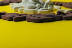 Mycket violet, ovala minnestavlor, spridda preventivpillerar, spridde på en gul bakgrund i form av en cirkel, i mitt av ciren Fotografering för Bildbyråer