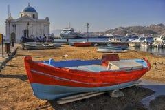 Myconos, Grecia, vista del cuadrado al lado de la iglesia local por el mar, en donde en el primero plano un barco de pesca rojo v foto de archivo