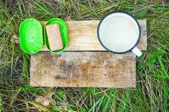 Mydło, mydlany naczynie i obmycie kubek na drewnianych deskach na trawy tle, zdjęcie stock