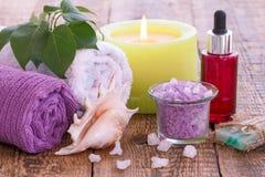 Mydło, płonąca świeczka, puchar z morze solą, butelka z aromatycznym olejem, bzów kwiaty i ręczniki na drewnianym tle, obrazy stock
