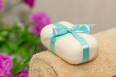 Mydło z błękitnym ribbin łękiem na ręcznika i witn purpurowych kwiatach na th Zdjęcia Stock