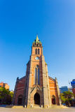 Myeongdong Cathedral Wide Front Courtyard. Centered front brick facade of Myeongdong Cathedral with clear blue sky on sunny spring day in Seoul, South Korea Royalty Free Stock Image