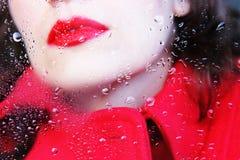 Myisteriousvrouw achter een vensterglas, waarover de regen neer daalt royalty-vrije stock fotografie