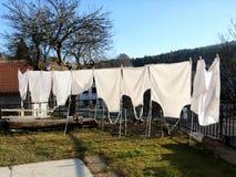 Myjący biali fartuchy suszą w gorącym słońcu w wiosce zdjęcia royalty free