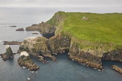 Mykines lighthouse and cliffs on Faroe islands from helicopter