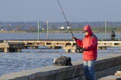 Mykolaiv, Ucrânia - 25 de março de 2017: As capturas do pescador pescam no cais da cidade fotos de stock