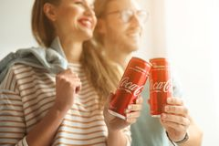 MYKOLAIV, UKRAINE - NOVEMBER 28, 2018: Young couple with Coca-Cola cans indoors. Refreshing drink stock images