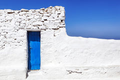 Mykonos Blue door in Whitewashed Wall Stock Photo